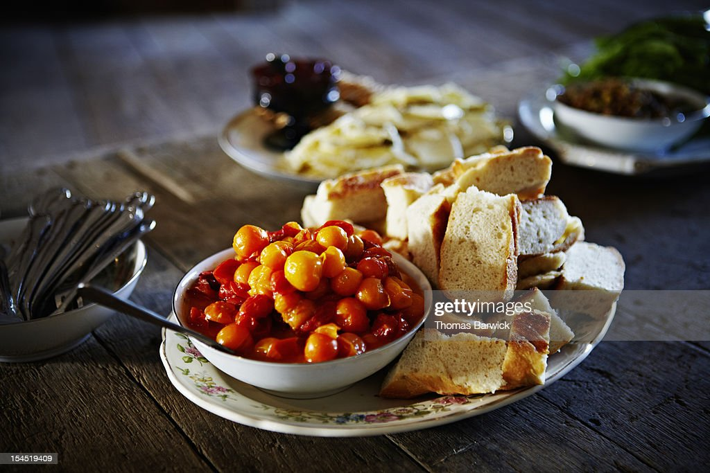 Bowl of pickled cherry tomatoes with slices bread : Stock Photo