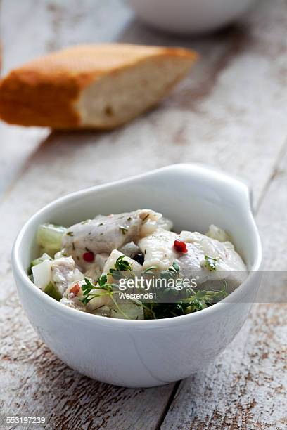 Bowl of pickled herring salad with cress