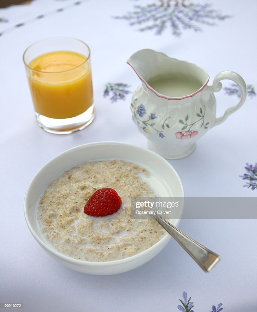 Bowl of porridge, jug of milk and glass of orange : Stock Photo