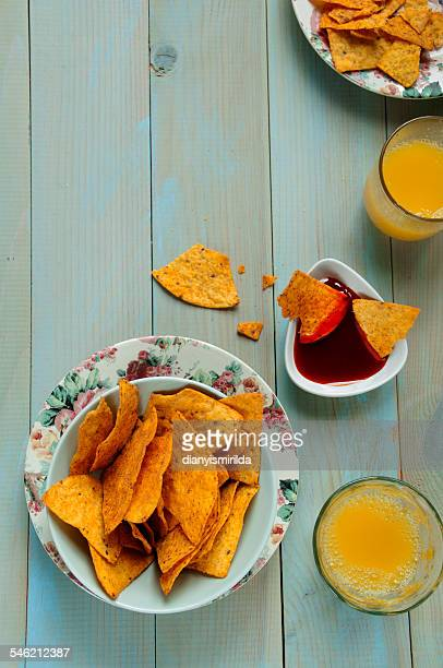 Bowl of potato chips, sauce and juice on table