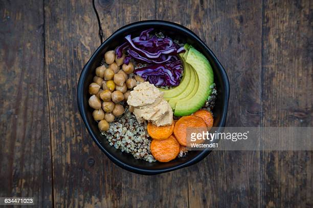 Bowl of quinoa, avocado, roasted chick-peas, sweet potato, red cabbage and hummus