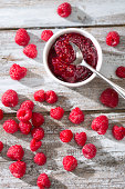 Bowl of raspberry jam, spoon and raspberries on wooden table, elevated view