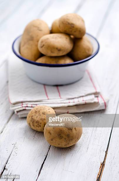 Bowl of raw potatoes on folded kitchen towel and wood
