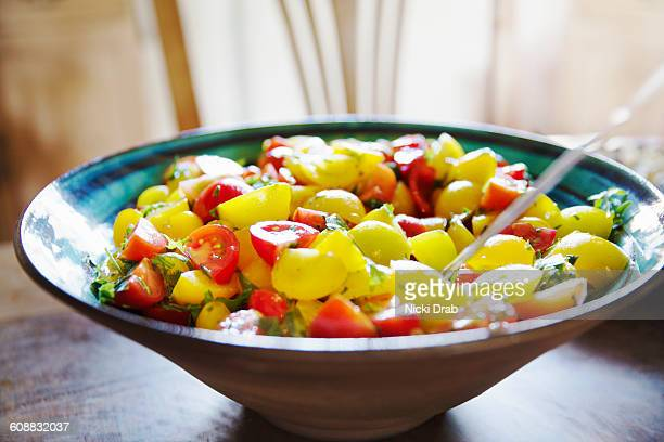 Bowl of red and yellow tomato salad kitchen table