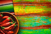 Red chili peppers fill a wooden bowl on vibrantly colored wood background