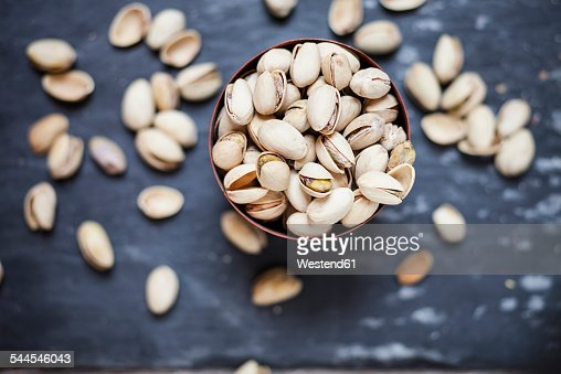 Bowl of roasted and salted pistachios on slate
