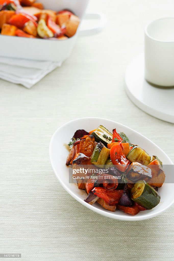 Bowl of roasted vegetables on table : Stock Photo