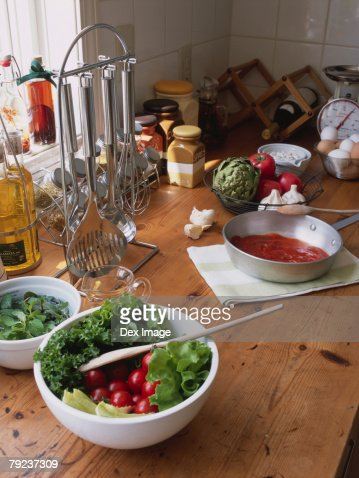 Bowl of salad and ingredients on kitchen table : Stock Photo