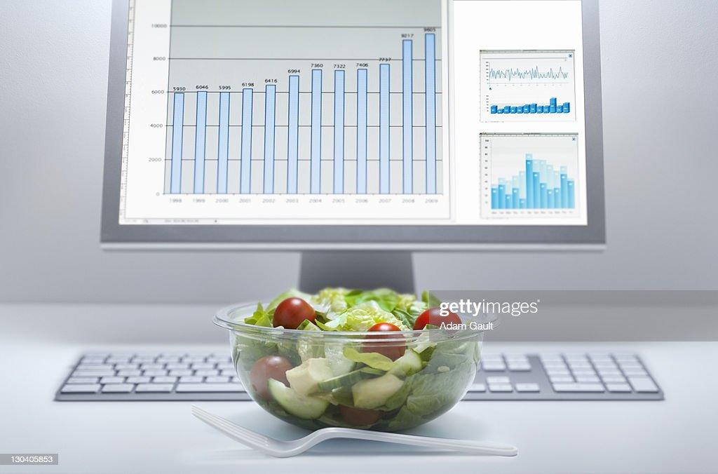 Bowl of salad at computer desk : Stock Photo