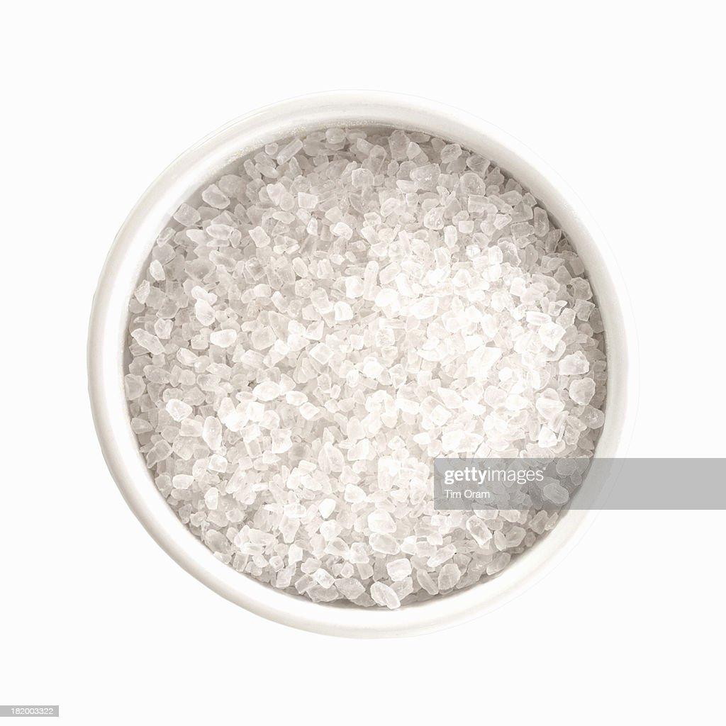 A bowl of salt granules on white