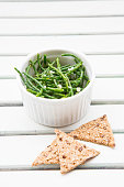 Bowl of saltwort salad and rye crackers on white wood