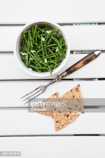 Bowl of saltwort salad, fork and rye crackers on white wood