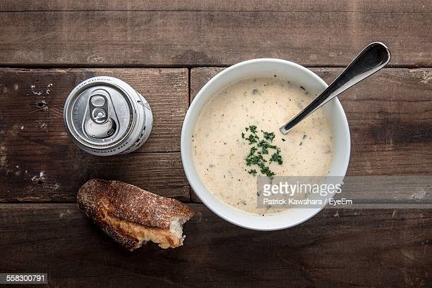 Bowl Of Soup, Can Of Beer And Bread On Wooden Table