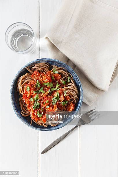 Bowl of spelt pasta with tomatoes and basil, glass of water, napkin and fork on white wood