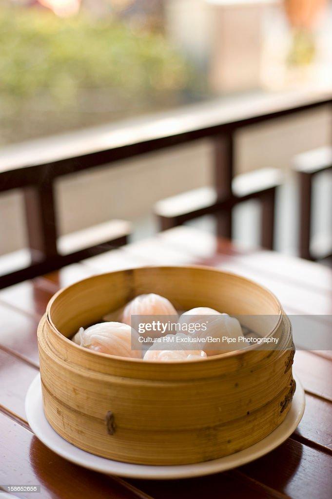 Bowl of steamed dumplings on table : Stock Photo
