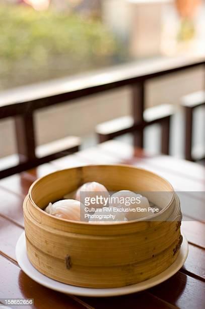 Bowl of steamed dumplings on table