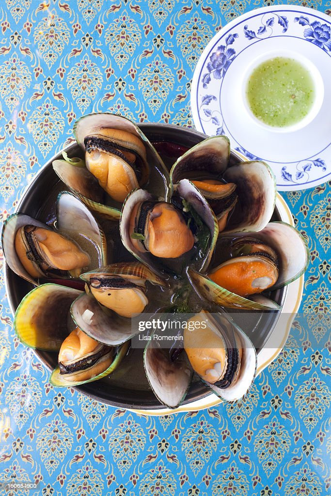 Bowl of steamed green mussels w/basil chili sauce : Stock Photo