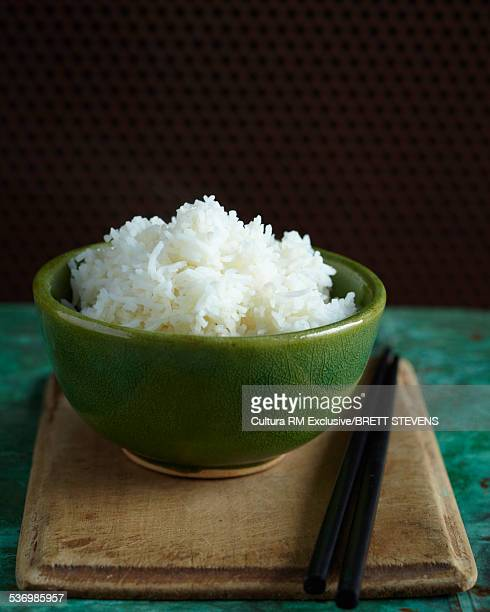 Bowl of steamed rice with chopsticks on chopping board