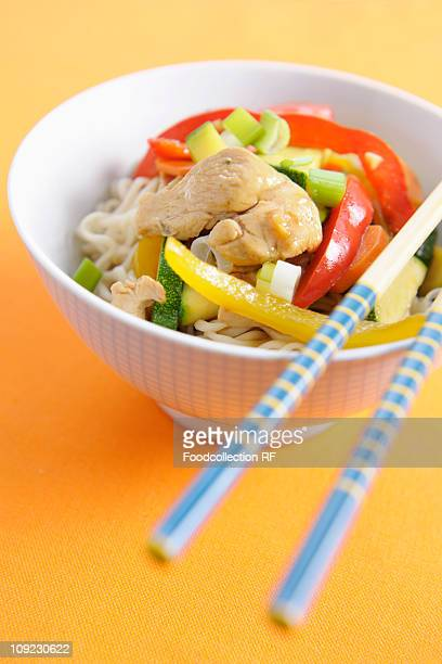 Bowl of stir-fried chicken and vegetables noodles, close-up