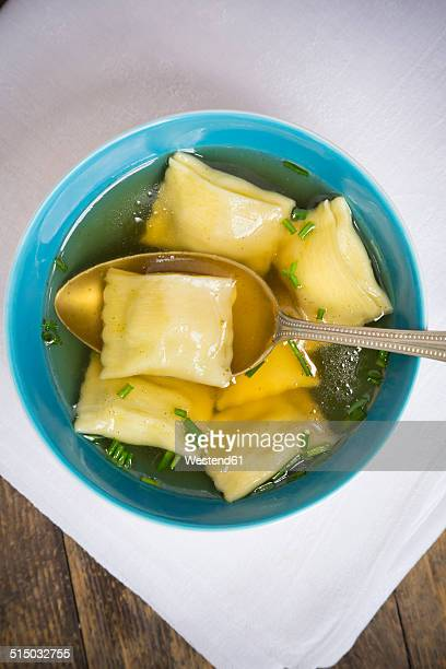 Bowl of stock with Swabian dumplings and spoon on white cloth, elevated view