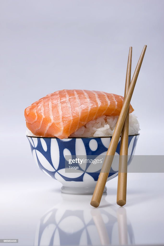 Bowl of sushi rice and piece of raw salmon