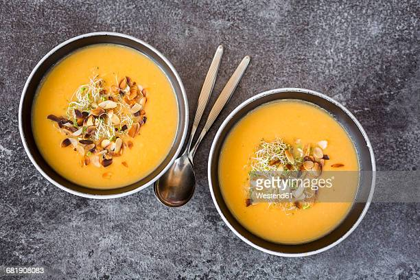Bowl of sweet potato coconut soup with ginger, parsnip, leek, sprout and almond