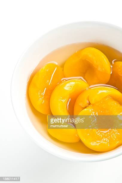 A bowl of tinned peaches on a white background