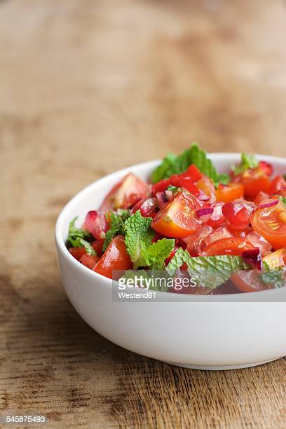 Bowl of tomato and pomegranate salad garnished with mint leaves on wood