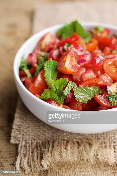 Bowl of tomato and pomegranate salad garnished with mint leaves on jute and wood