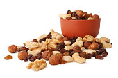 Nuts and raisins with terracotta bowl isolated on white background.