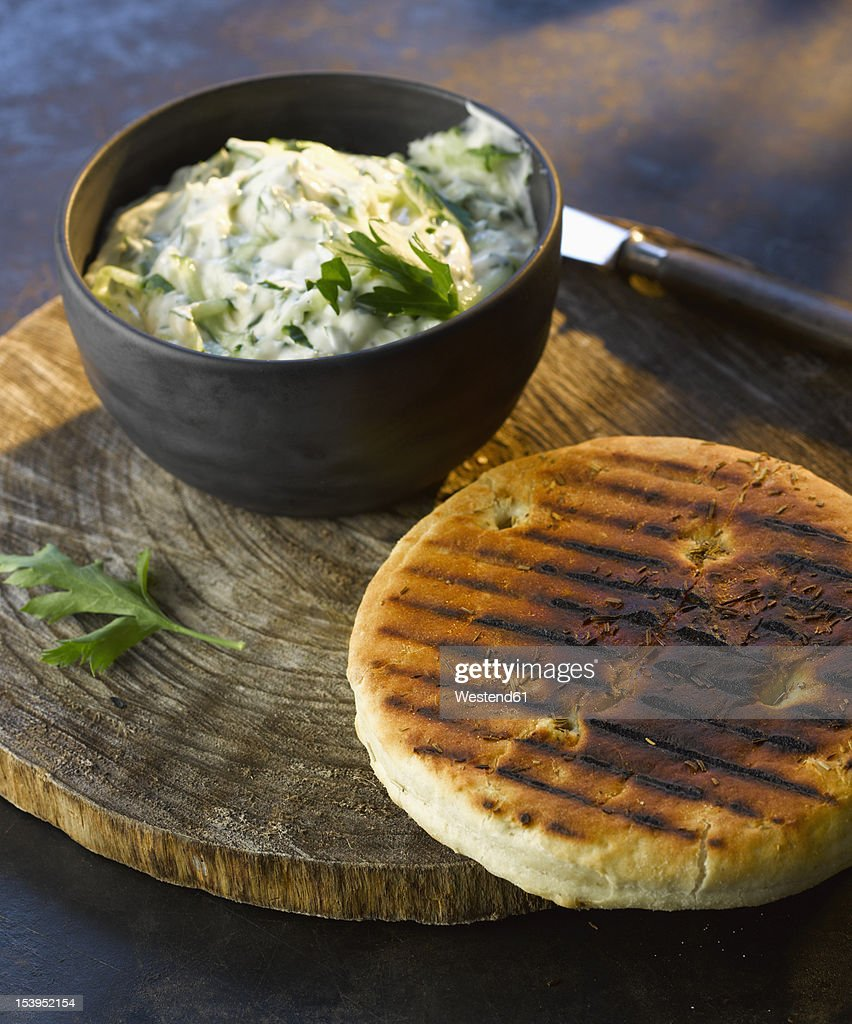 bowl of tzatziki with grilled bread on wooden board, close up