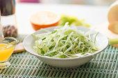 Bowl of vegan healthy raw vegetable salad - daikon radish, celery, cucumber and spring onions - organic cuisine. Close-up.