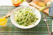 Bowl of vegan healthy raw vegetable salad - daikon radish, celery, cucumber and spring onions - organic japanese cuisine. Close-up.
