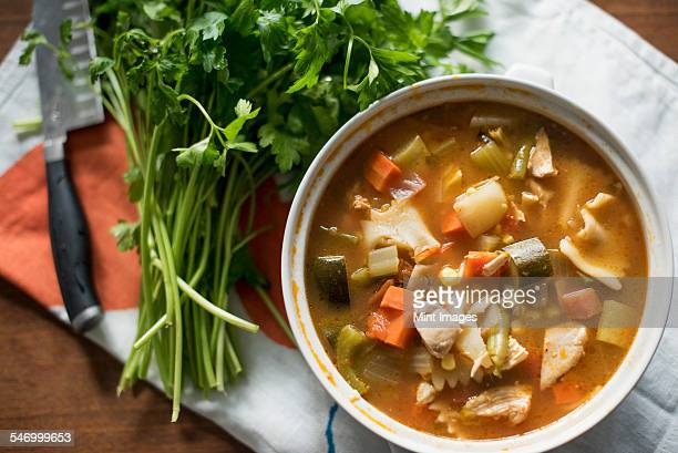 A bowl of vegetable stew and a bunch of fresh herbs on a table.