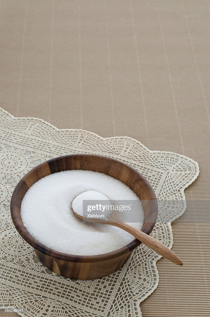Bowl of white sugar with wooden spoon. : Stock Photo