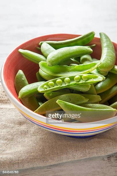Bowl of whole and opened peasecods of snow peas on cloth and wood