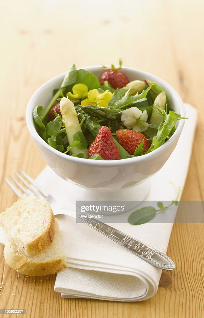Bowl of wild herbs salad with asparagus and strawberries : Stock Photo