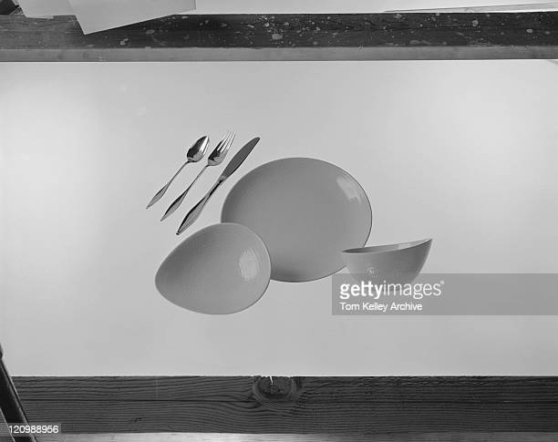 Bowl, plate, spoon, fork and butter knife on white background