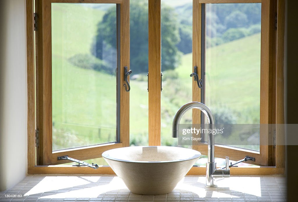 Bowl sink at window in bathroom : Stock Photo