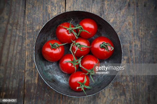 Bowl with cherry tomatoes on wooden table, elevated view
