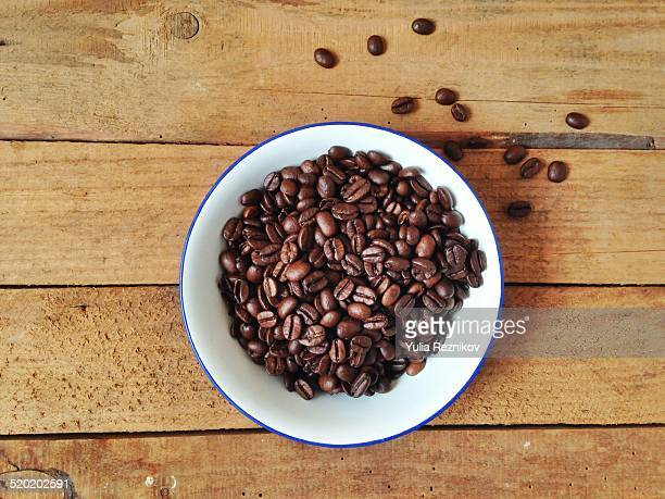 Bowl with coffee beans on the wood background
