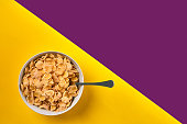 Food, healthy eating, people and diet concept. Bowl with corn flakes and spoon on purple and yellow background, top view. Copy space. Still life. Flat lay.