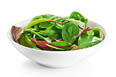 Bowl with fresh green salad isolated on white background. Salad mix with spinach, rucola, mangold and lamb's lettuce.
