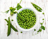 Bowl with fresh peas on a wooden background