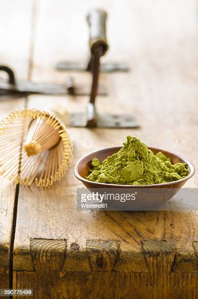 Bowl with matcha powder and a tea whisk on wood