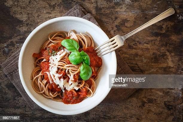Bowl with spelt whole grain spaghetti, tomato sauce, parmesan and basil