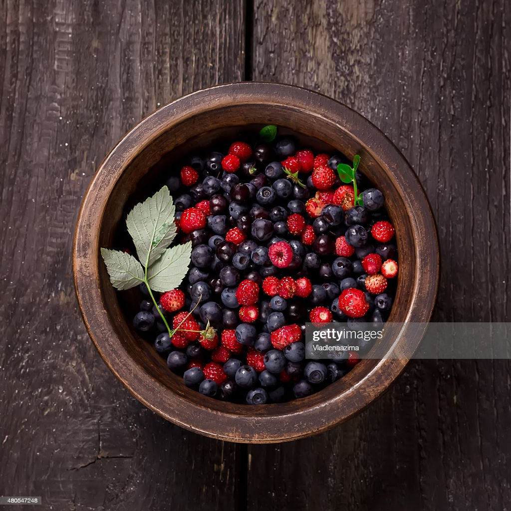 Bowl with wild berries on dark wooden background. Style rustic. : Stock Photo