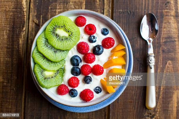 Bowl with yogurt and blueberries, kiwi, mango and raspberries, spoon on wood