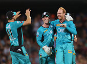 Bowler Jason Floros of the Heat is congratulated by his teammates after dismissing Ben Dunk of the Hurricanes during the Big Bash League match...