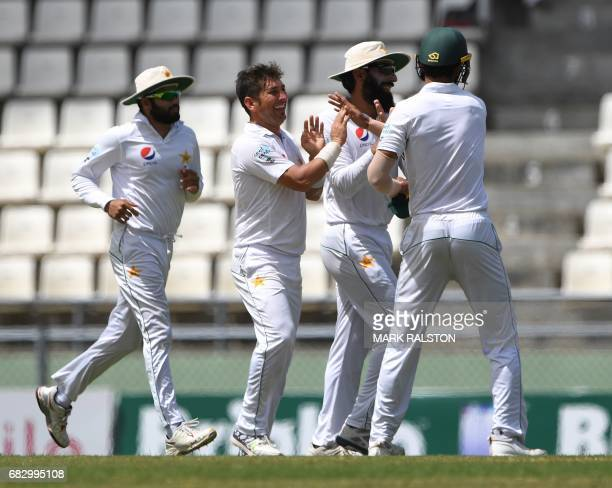 Bowler Yasir Shah of Pakistan celebrates with teammates after taking the wicket of West Indies batsman Kraigg Brathwaite who was caught by Hasan Ali...